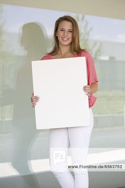 Europe  Germany  North Rhine Westphalia  Duesseldorf  Young woman with placard  smiling  portrait