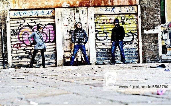 3 junge Leute posieren vor Graffitifassade