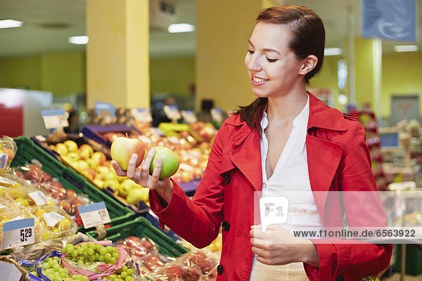 Young woman comparing apples in supermarket