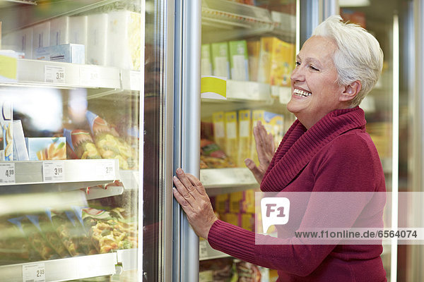Reife Frau im Supermarkt am Gefrierschrank stehend