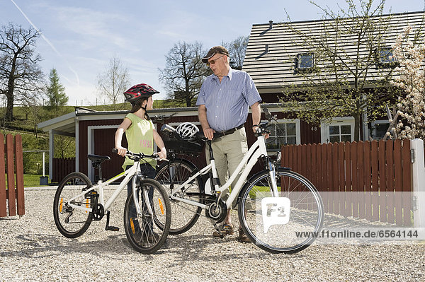 Germany  Bavaria  Grandfather and granddaughter standing with electric bicycle