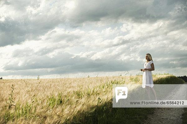 Mature woman standing in grain field