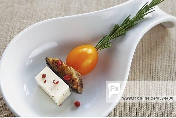 Auberginen-Feta-Spiesse mit Basilikum auf einem Weinglas
