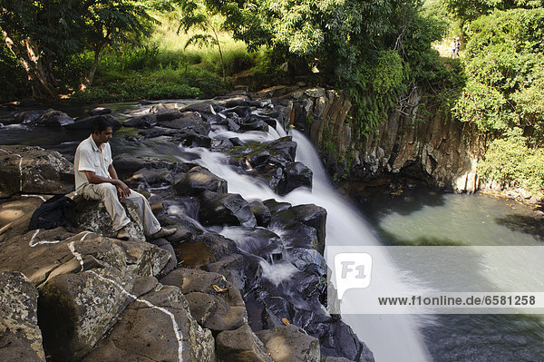Eine Frau sitzt am Rochester Wasserfall  Soulliac  Mauritius *** Local Caption ***
