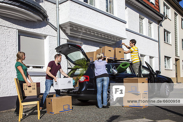 Private house move  people loading a station wagon  friends helping