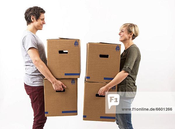 Junges Paar trägt Umzugskartons  Umzugskisten