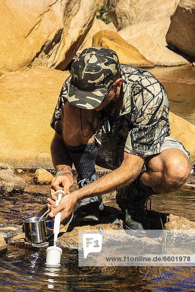 Wanderer filtert Wasser am Brandberg  Damaraland  Namibia  Afrika