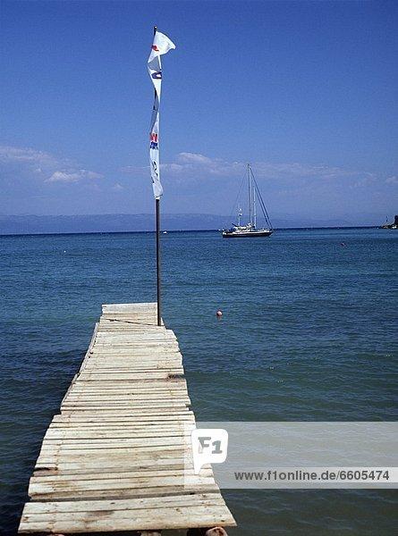 Flag On Wooden Pier At Lakka Beach