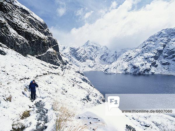 Woman Walking In A Snowy  Mountainous Landscape
