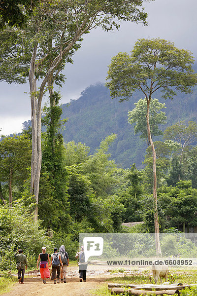 Tourists Walking Beneath Mountains On Bolaven Plateau