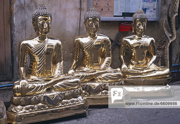 Three Golden Buddha Statues Lined Up