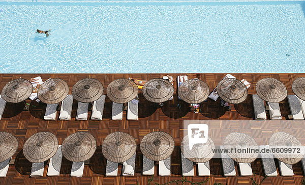 Man Swimming In Pool By Sunloungers  Aerial View