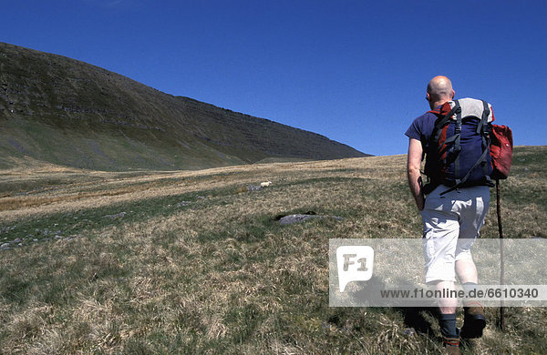Hiker With Walking Stick On Black Mountain  Rear View