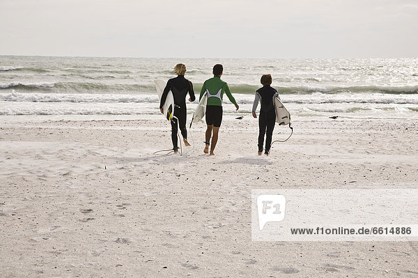 Three surfers on Lido Beach