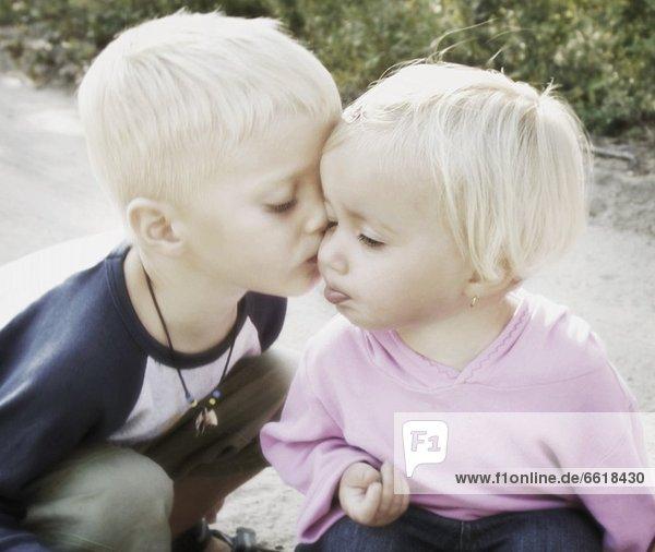 Junge - Person  küssen  Mädchen