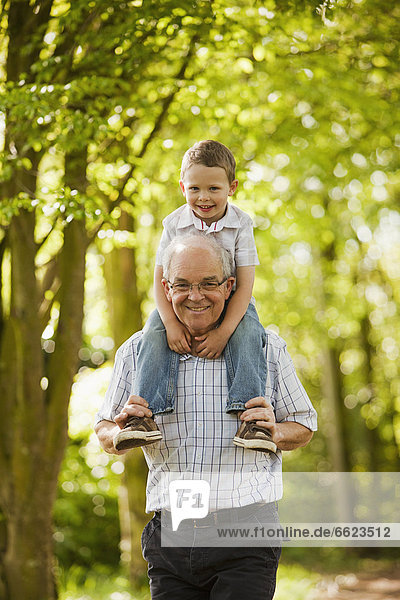 Caucasian grandfather carrying grandson on shoulders
