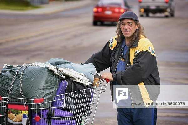 Homeless Man With His Belongings In Shopping Trolley