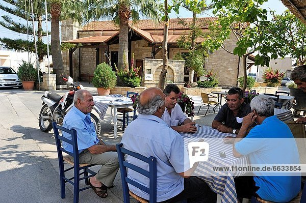 men playing card game outside cafe of Kouklia  Paphos district  Cyprus  Eastern Mediterranean Sea