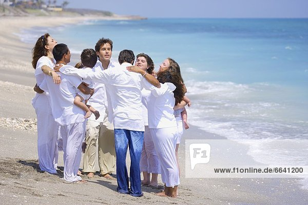 A Group Of People Pray Together At The Beach