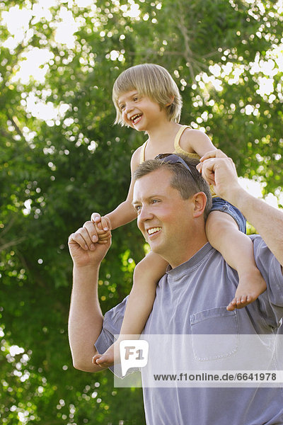 A Little Girl Rides On Her Fathers Shoulders