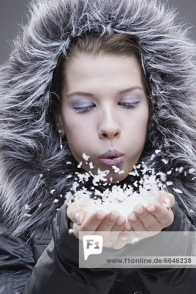 Young Woman In Fur Lined Jacket  Breathing Onto A Handful Of Snow