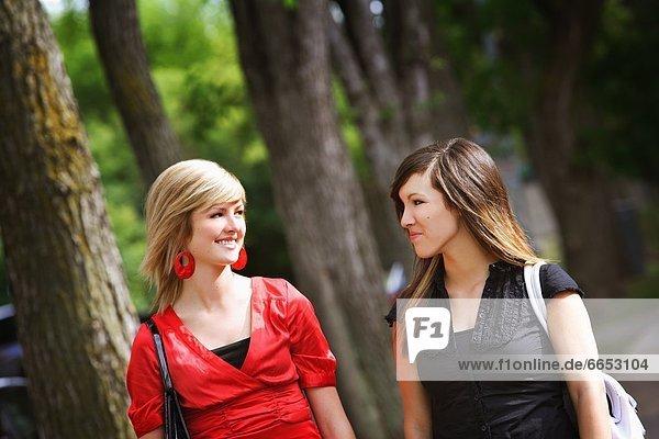 Two Women Walking In The Park