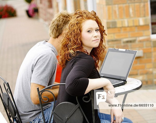 Couple Working On Laptop Outside