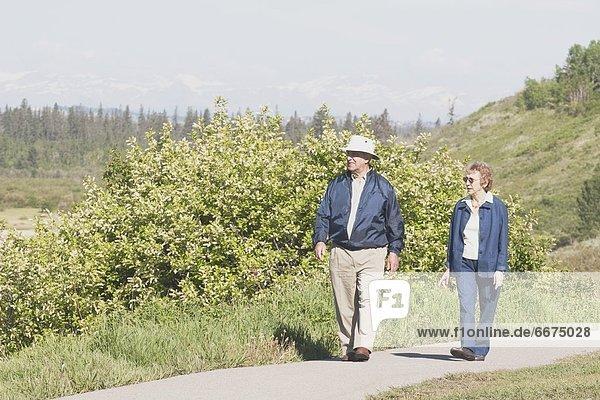 Elderly Couple Walking On A Path