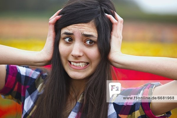 A Girl Holding Her Head With A Crazy Face