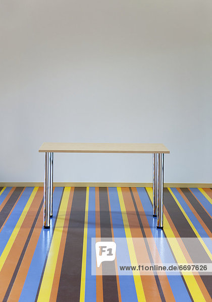 Table Standing on a Striped Floor