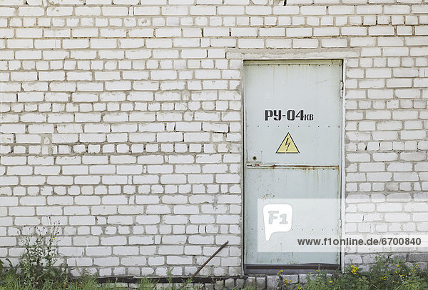 Factory Entrance With a Warning Sign