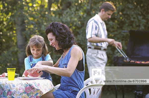 Mother And Daughter Eating Watermelon At Picnic