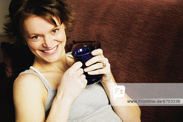Woman Holding Coffee And Smiling