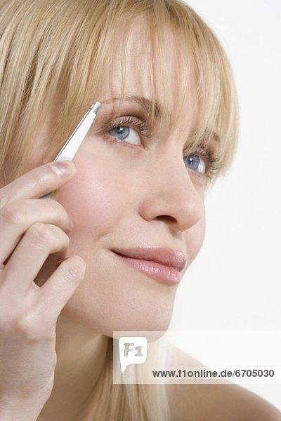 Frau Augenbrauen zupfen