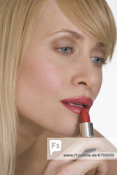 eincremen verteilen Frau Lippenstift rot auftragen mund
