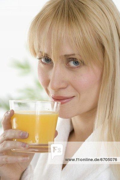 Frau im Bademantel trinken Orangensaft