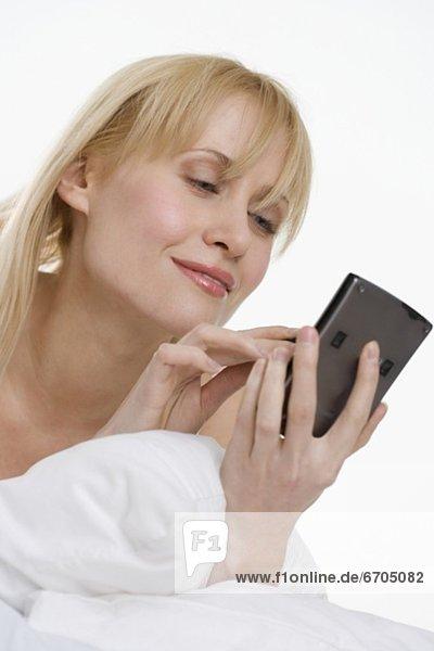 Personal Digital Assistant  PDA  Electronic Organizer. Palmtop  benutzen  Frau  Bett