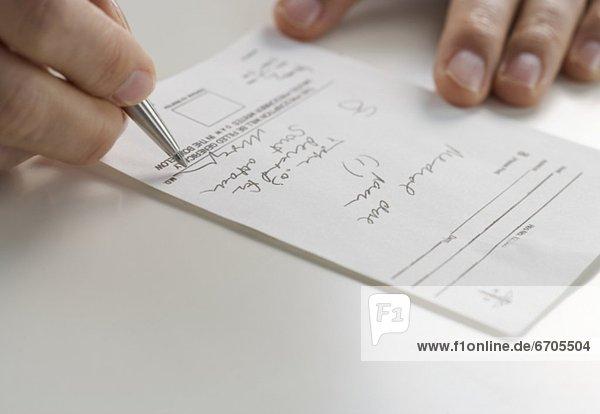 Closeup of hands signing prescription