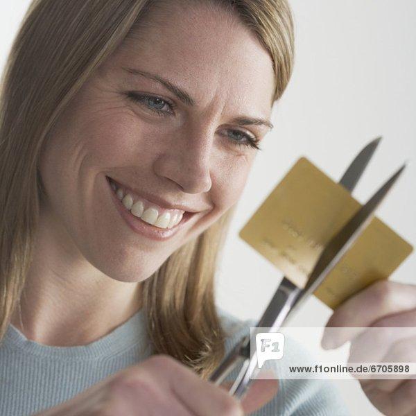 Frau zerschneiden Kreditkarte