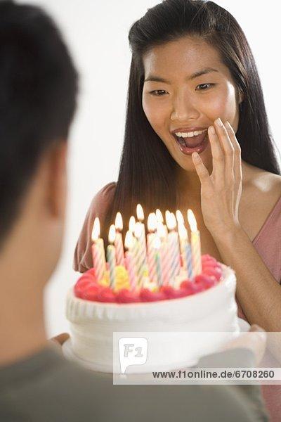 Frau präsentiert mit Überraschung Geburtstagstorte