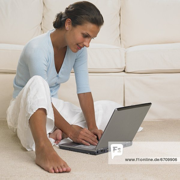 Woman using laptop on floor