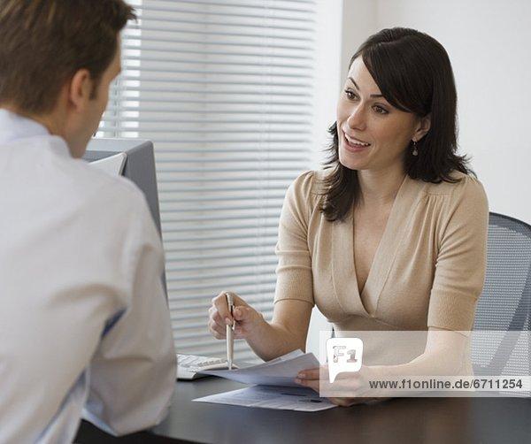 Geschäftsfrau  Schreibtisch  sprechen  Kollege
