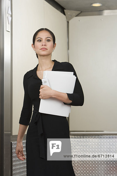 Geschäftsfrau steht in Aufzug