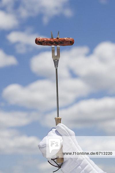 Hot dog on barbeque fork