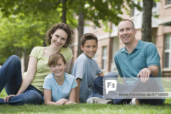 Family with two children sitting on grass