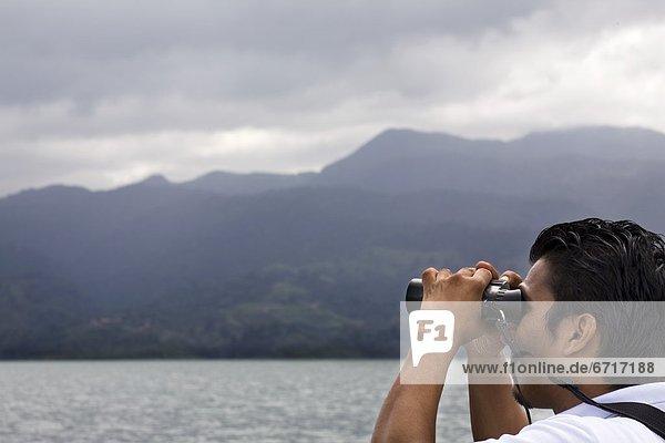 Hispanic Man Looking Through Binoculars  Costa Rica