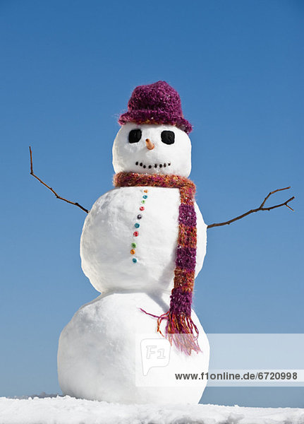 Snowman wearing hat and scarf  clear sky in background