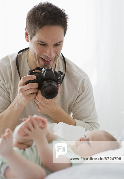 Father taking photograph of baby