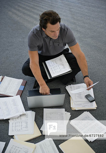Man sitting on floor with laptop with documents around
