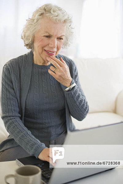 Vereinigte Staaten von Amerika USA Senior Senioren benutzen Frau Notebook Zimmer Wohnzimmer